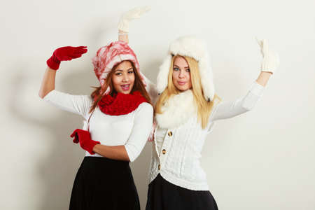 Fashion winter outfit concept. Two girls blonde and mulatto in warm red white clothing having fun. Attractive women wearing fur caps, scarfs, gloves.
