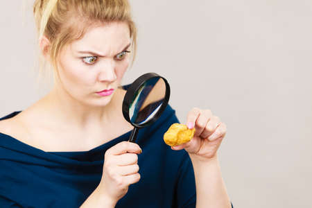Blonde woman holding magnifying glass investigating piece of bread. Gluten products, food ingredients and pesticides concept.