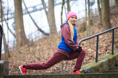 Outdoor sport exercises, sporty outfit ideas. Woman wearing warm sportswear training exercising, stretching legs outside during autumn.