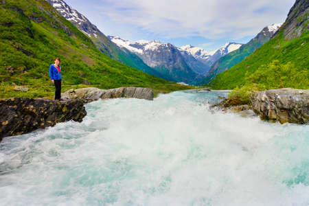 Travel, beauty in nature. Tourist woman looking at Videfossen (called Buldrefossen) waterfall in Norway Sogn og Fjordane