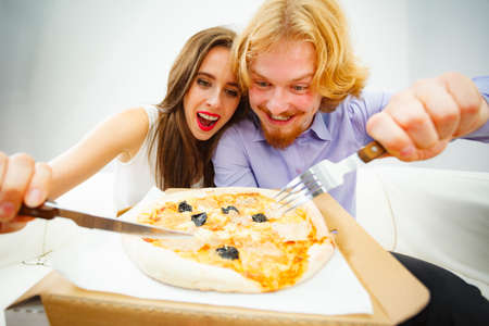 Funny crazy man and woman spending time together. Cheerful couple or friends eating delicious cheesy pizza.