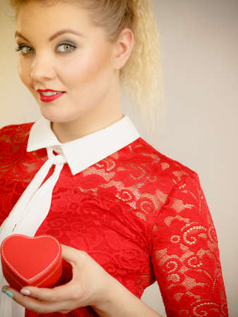 Happy joyful blonde woman with tied hair in pony tail holding valentines gift in heart shaped box. Female having beautiful make up.
