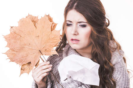 Sick freezing woman holding maple leaves, sneezing in tissue. Girl being cold trembling. Seasonal disease flu or other virus. Health care, immunity concept.