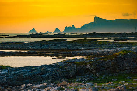 Seascape on Andoya island. Scenic rocky coastline with mountain peaks in distance, view from Bukkekjerka rest stop area, Vesteralen archipelago, Norway.