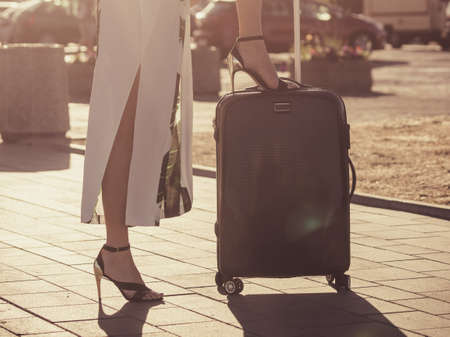 Fashionable woman arriving to new city wearing long dress and high heels, holding her suitcase on wheels admiring town after arrival. Foto de archivo