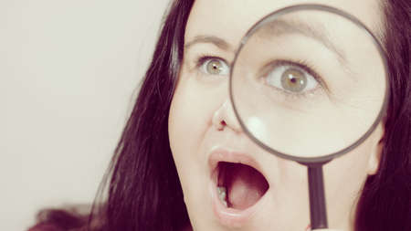 Shocked adult woman holding magnifying glass investigating something and looking closely, trying to find solution.