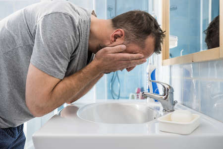 Man splashing water on his face, washing himself, taking care of personal hygiene. Feeling fresh in the morning Stock Photo