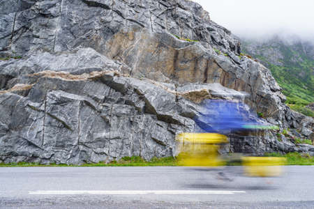 Biker cyclist driving riding in high speed, sport person blurry taking part of sports competition in Norway mountains. Reklamní fotografie