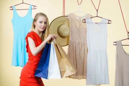 Woman in clothes shop store holding shopping bags picking summer perfect outfit, dress hanging on clothing hangers