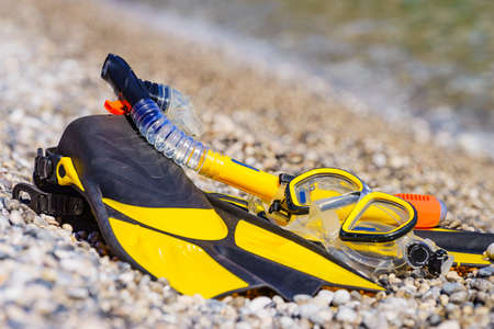 Snorkel equipment flippers and snorkeling mask tube lying on stone beach sea shore. Summer vacation swimming fun concept. 写真素材
