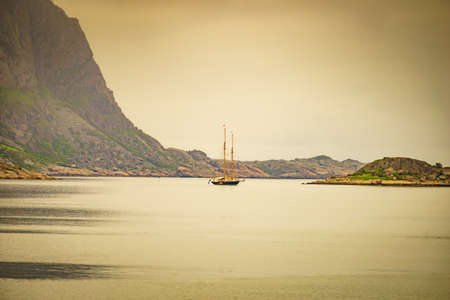 Sailing ship on water sea, norwegian fjord nature. Cruising, travel by sailboat, vacation trip for pleasure. Lofoten Norway