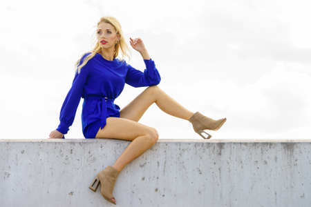 Fashionable woman wearing blue jumpsuit shorts perfect for summer. Fashion model outdoor photo shoot Stock Photo