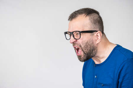 Adult man wearing eyeglasses yelling at somebody. Side profile view with copy space Stockfoto