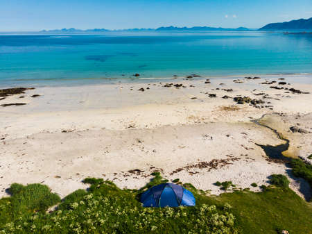Blue tent on Gimsoysand sandy beach in summer. Camping on ocean shore. Lofoten archipelago Norway. Holidays and travel. Stock Photo