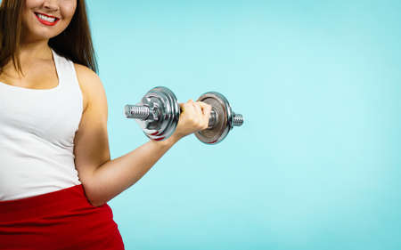 Fitness and building muscles resolution. Woman lifting dumbbells weights, on blue. Goal achievement in training.