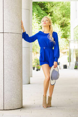 Fashionable woman wearing blue jumpsuit shorts perfect for summer holding elegant stylish sun hat. Fashion model outdoor photo shoot