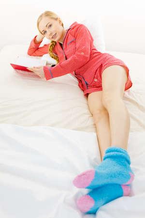 Dziewczyna leży w łóżku, czytanie książki. Młoda blond kobieta nosi czerwone kropkowane piżamy niebieskie ciepłe skarpetki relaks w domu na materacu. Zdjęcie Seryjne