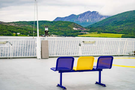 Ferry deck with empty seats and sea view. Ferryboat ride route Bognes - Lodingen to Lofoten islands Norway. Tourism vacation and travel. Stock Photo