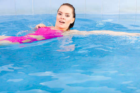Beautiful young woman in pink swimsuit swimming in blue pool on her back. Young female swimmer at holiday resort. Sport activity health concept. 写真素材
