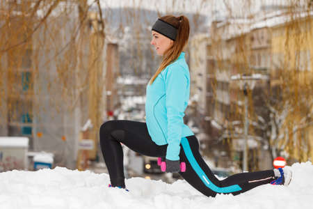Girl wearing sportswear and doing stretching exercises on snow with urban background. Winter sports, outdoor fitness, fashion, workout, health concept. 写真素材