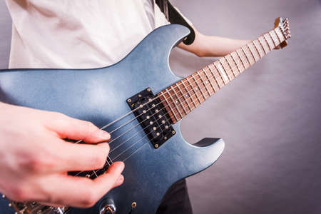 Close up of man playing on electric guitar during gig or at music studio. Musical instruments, passion and hobby concept. Stockfoto