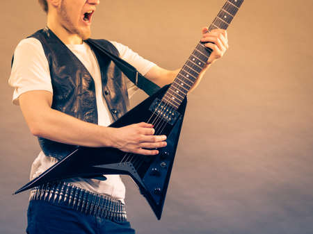 Teen hardcore man wearing metal outfit playing on electric guitar heavy rock music having yelling screaming face expression.
