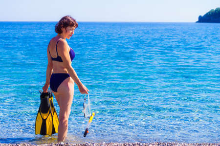 Mature female with snorkel equipment flippers and snorkeling mask tube on beach sea shore. Summer vacation swimming fun concept.