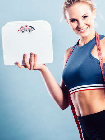 Fitness woman with measure tape holding weight scale studio shot blue background