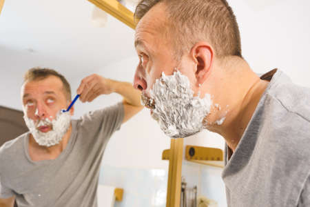 Man with lots of shaving foam on his face standing in bathroom, looking at mirror, shaving his face beard. Skincare Banco de Imagens