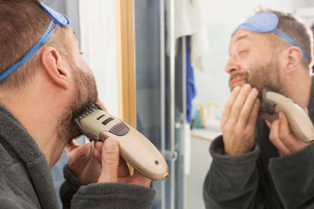 Funny mature adult man looking at himself in mirror trimmng, shaving his beard using electric timmer razor. Banco de Imagens