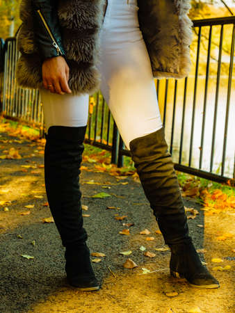 Unrecognizable woman wearing warm long dark fur vest. Autumnal fashion, autumn season styled outfits. Female having a walk in park