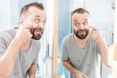 Happy funny adult guy applying moisturizer cream for male skin care. Man in front of bathroom mirror with anty aging lotion on face. Banco de Imagens