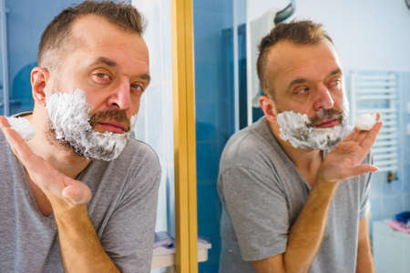 Man applying shaving foam cream on his face, standing in bathroom, looking at mirror, preparing to shave his face beard. Skincare Banco de Imagens