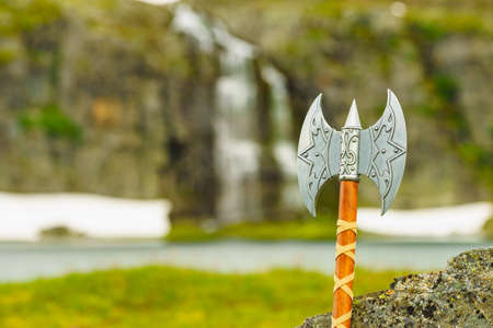 Equipment of viking or barbarian warrior outdoor on nature. Viking axe against norwegian nature. Tourism and traveling concept