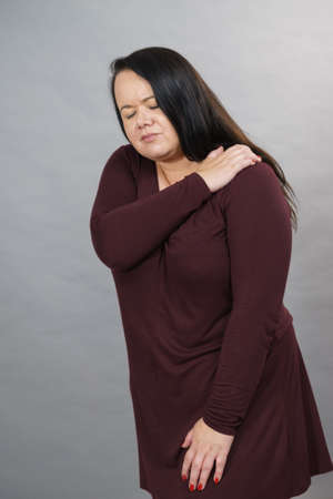 Adult woman feeling pain in shoulder, female with arm ache having problem. Joints health concept. 写真素材