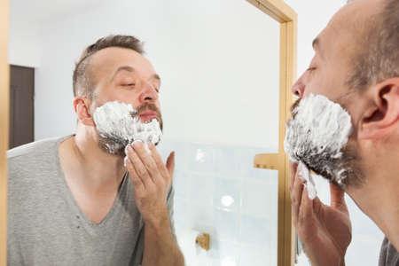 Man preparing his facial hair before trimming his beard, applying shaving cream foam mousse. Male beauty treatment concept.