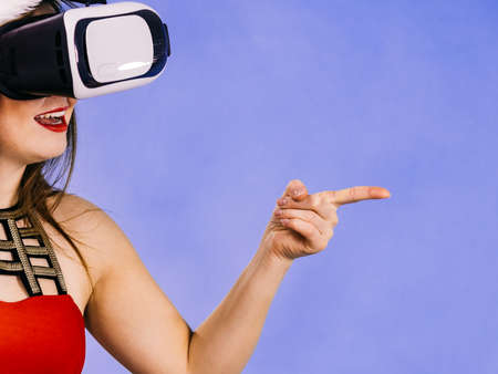 Woman wearing santa claus hat exploring space with virtual reality goggles headset. Amazed girl watching 3d film tour in vr glasses box. New generation cyber christmas concept, on blue.