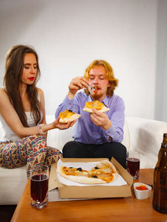 Man and woman spending time together. Couple or friends eating delicious cheesy pizza. Stock Photo