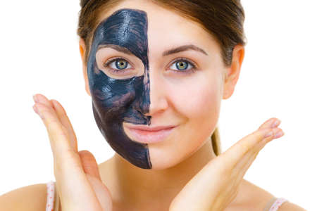 Woman with clay carbo detox black mask on her face, on white. Girl taking care of oily skin complexion. Beauty treatment. Skincare. Фото со стока
