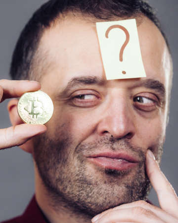Adult man questioning crypto currency having doubtful sign on his head holding bitcoin symbol. Thinking of earning internet money.