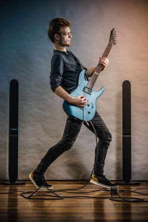 Young bearded man with electric guitar. Adult person in full length is holding instrument and playing. Hobby, music concept, on grey Stock Photo - 129680188