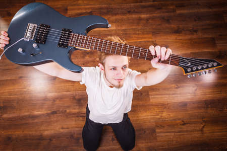 Young bearded man holding, raising his electric guitar. Hobby, music concept, on wooden floor. View from top Stock Photo - 129679684