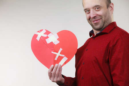 Healed love. Valentines Day concept. Adult smiling man holding big red heart fixed with plaster bandage. Male healing relationship.