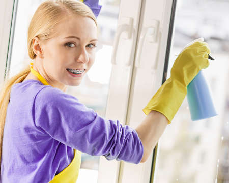 Young housewife cleaner woman washing window at home using cloth and spray detergent. Cleaning concept Banque d'images - 129680319