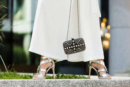 Unrecognizable woman wearing fashionable outfit. Close up at silver high heels, white culottes trousers and small black bag purse with pearls 版權商用圖片