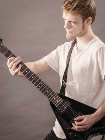 Man playing on electric guitar during gig. Musical instrument. Teenage boy having music hobby. Stock Photo - 129680008