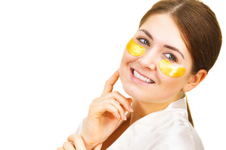 Woman applying golden collagen patches under eyes, on white. Mask removing wrinkles, dark circles. Girl taking care of delicate skin around eye. Beauty treatment. Banco de Imagens