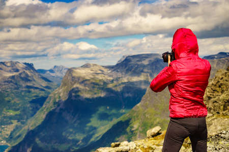 Tourism vacation and travel picture. Female tourist taking photo with camera, enjoying nature from Dalsnibba mountain viewpoint at windy day, Norway.