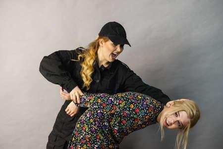 Il taccheggio è un crimine. Giovane donna alla moda sorpresa a rubare vestiti da una guardia giurata femminile. Il cliente è ladro.