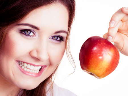 Woman holding red apple fruit in hand close to face, smiling, isolated on white. Healthy eating, high fibre diet concept. Stock Photo